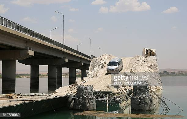 TOPSHOT Members of the Syrian Democratic Forces alliance stand guard next to a bridge that was destroyed by the Islamic State group after they took...