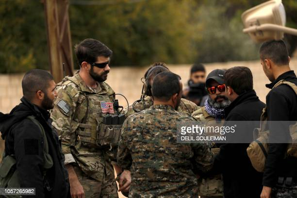 Members of the Syrian Democratic Forces and US soldiers gather in the Kurdishheld town of AlDarbasiyah in northeastern Syria bordering Turkey on...