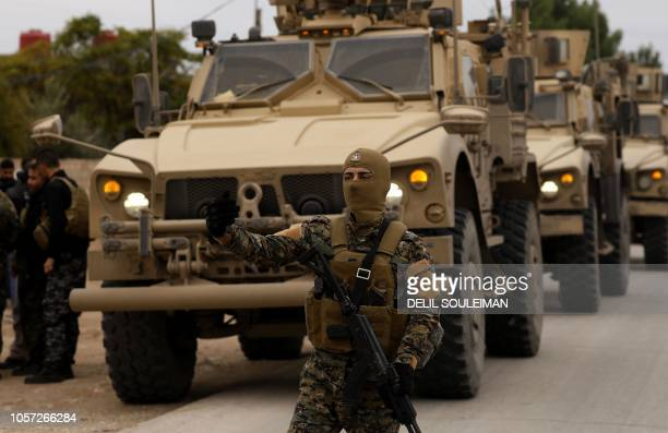 Members of the Syrian Democratic Forces and US soldiers patrol the Kurdishheld town of AlDarbasiyah in northeastern Syria bordering Turkey on...