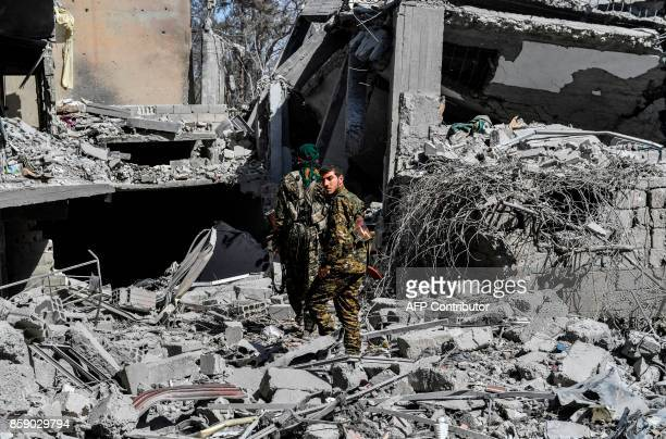 Members of the Syrian Democratic Forces backed by US special forces make their way through the rubble on the western frontline of Raqa on October 8...