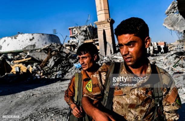 TOPSHOT Members of the Syrian Democratic Forces backed by US special forces check the area near Raqa's stadium as they clear the last positions on...