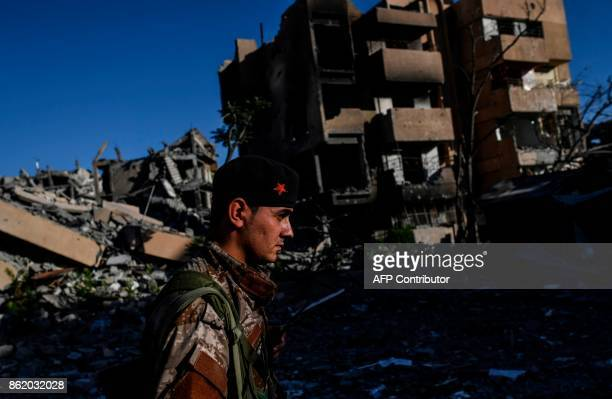 Members of the Syrian Democratic Forces backed by US special forces check the area near Raqa's stadium as they clear the last positions on the...