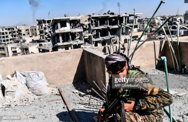 Members of the Syrian Democratic Forces backed by US special forces walk on a building near Raqa's central hospital as they clear the last positions...