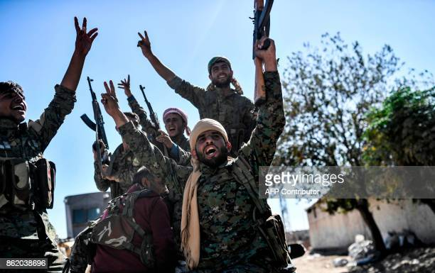 Members of the Syrian Democratic Forces , backed by US special forces, celebrate at the frontline in the Islamic State group jihadists crumbling...