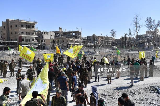 Members of the Syrian Democratic Forces backed by US special forces gather at the iconic AlNaim square in Raqa on October 17 2017 USbacked forces...
