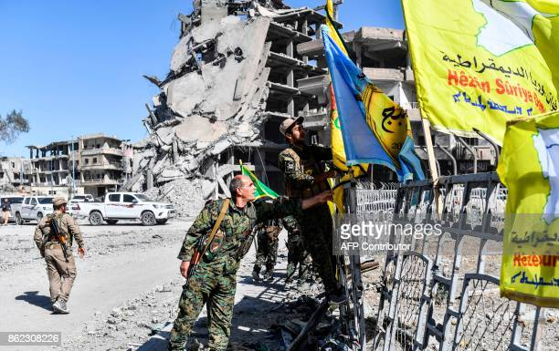Members of the Syrian Democratic Forces backed by US special forces place their flags at the iconic AlNaim square in Raqa on October 17 2017 USbacked...