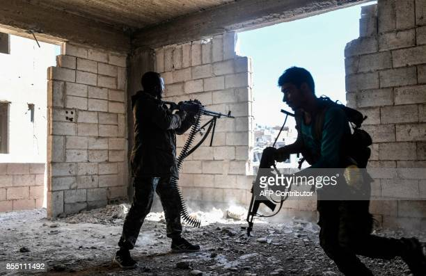 Members of the Syrian Democratic Forces fire their arms during a battle against Islamic State group jihadists to retake the central hospital of Raqa...