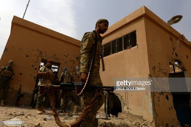 Members of the Syrian Democratic Forces gather next to a building in the village of Susah in the eastern province of Deir Ezzor near the Syrian...