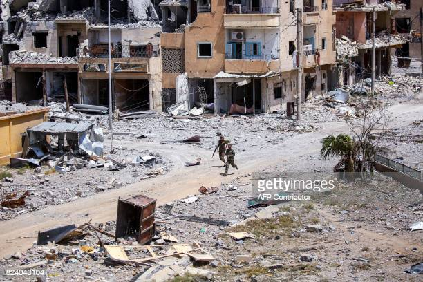 Members of the Syrian Democratic Forces move through destroyed buildings in Raqa on July 28 2017 The SDF a USbacked KurdishArab alliance has ousted...