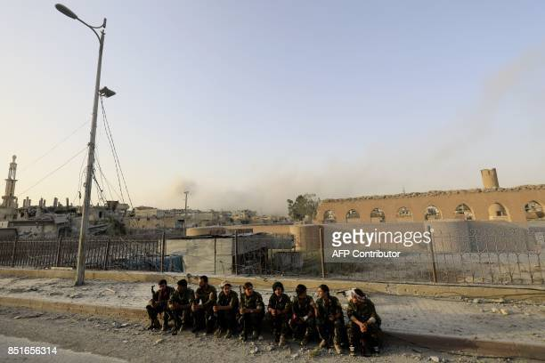 Members of the Syrian Democratic Forces sit on a damaged street in the former Islamic State stronghold of Raqa on September 22, 2017. The US-backed...