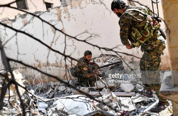 TOPSHOT Members of the Syrian Democratic Forces Syrian fighters backed by US special forces search newly taken areas near the central hospital of...