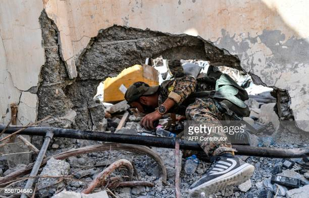 Members of the Syrian Democratic Forces Syrian fighters backed by US special forces search newly taken areas near the central hospital of Raqa on...