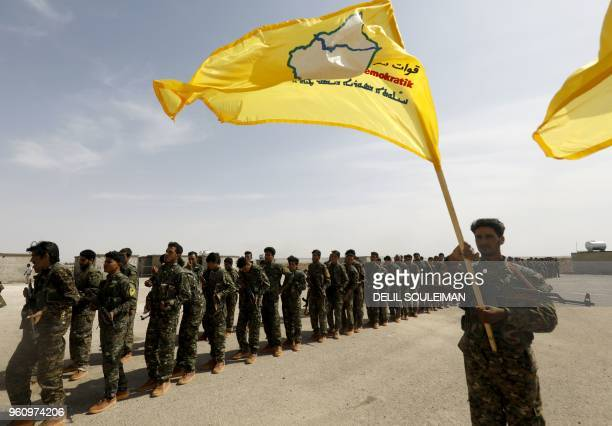 Members of the Syrian Democratic Forces trained by the USled coalition participate in the graduation ceremony of their first regiment in alKasrah in...