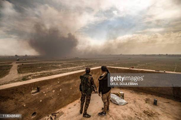 Members of the Syrian Democratic Forces watch as smoke plumes billow after shelling on the Islamic State group's last holdout of Baghouz, in the...