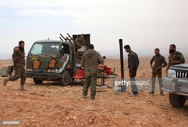Members of the Syrian government forces chat after they retook the village of Jihar and the surrounding hills from Islamic State group fighters in...
