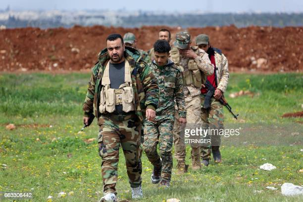 Members of the Syrian government forces march near the town of Qumhanah in the countryside of the central province of Hama on April 1 2017 Syrian...