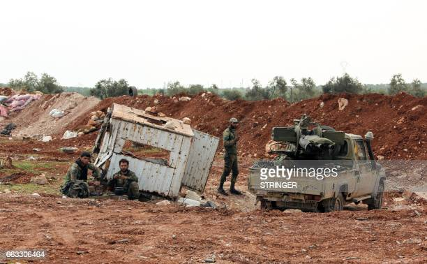 Members of the Syrian government forces rest by their vehicles near the town of Qumhanah in the countryside of the central province of Hama on April...