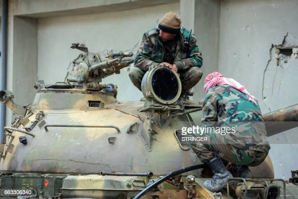 Members of the Syrian government forces sit over the turret of a tank near the town of Qumhanah in the countryside of the central province of Hama on...