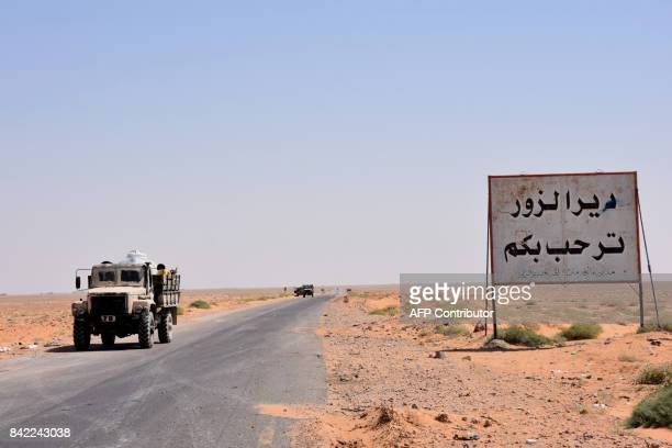 Members of the Syrian government forces stand on the entrance to Deir Ezzor city on September 3 2017 The writing in Arabic reads 'Welcome to Deir...