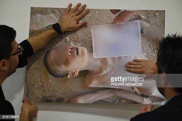 Members of the Syrian Organisation for the Victims of War display pictures documenting the torture of detainees inside the Assad regimes prisons and...