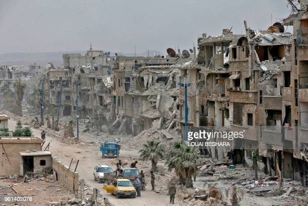 TOPSHOT Members of the Syrian progovernment forces inspect the damage of a street in the Hajar alAswad neighbourhood on the southern outskirts of the...