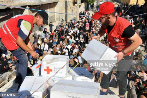 Members of the Syrian Red Crescent distribute humanitarian aid parcels to local residents in the northeastern city of Deir Ezzor on September 9 2017...