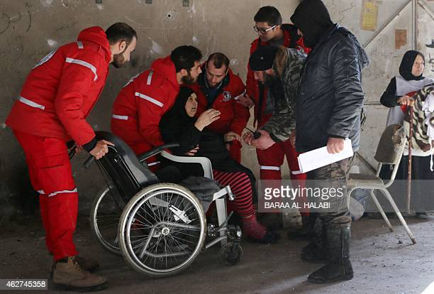Members of the Syrian Red Crescent prepare to transport Syrians from a rebelcontrolled area to a regime held area of the northern Syrian city of...