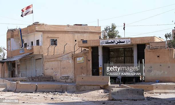 Members of the Syrian regime forces stand at the entrance of a detention centre in the northeastern Syrian city of Hasakeh's Ghweran neighborhood on...