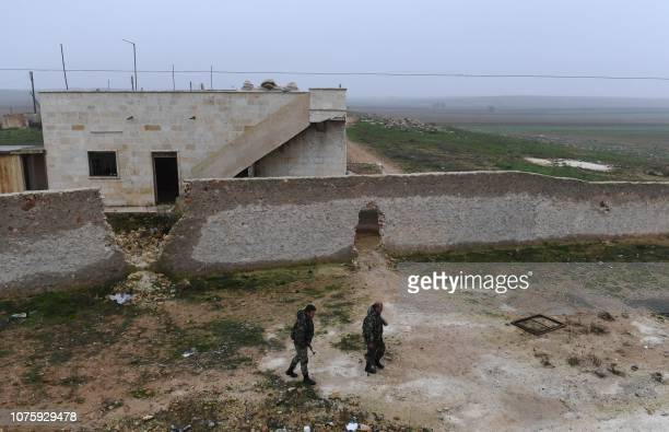 Members of the Syrian regime forces walk near buildings in the southern countryside of the northern Kurdishcontrolled city of Manbij on December 30...