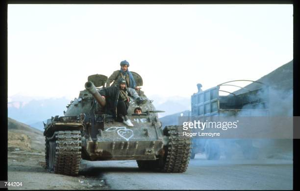 Members of the Taliban army ride a tank on a road toward Charikar and Bagram Base October 21 1996 near Kabul Afghanistan The Taliban army faces...