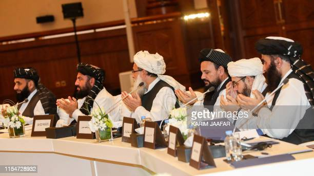 Members of the Taliban attending the second day of the Intra Afghan Dialogue talks raise their hands as they recite a prayer while seated during the...