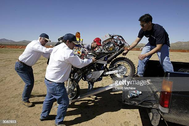 Members of The Team Blue pack up their DexteritGhost Rider motorcycle autonomous or unmanned vehicle to go home after it failed at the starting line...