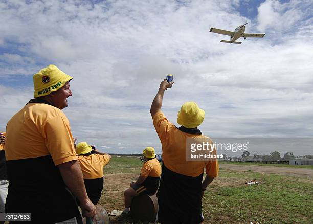 Members of the team 'Coral Coast Marine Madmans' wave to a plane that has just taken off over their cricket pitch during the Goldfield Ashes January...