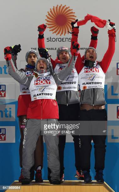 Members of the team of Poland celebrate on the podium after the Men's Large Hill Team Ski Jumping event of the 2017 FIS Nordic World Ski...