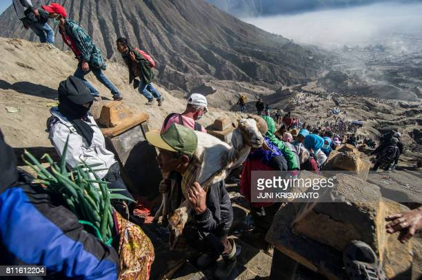 TOPSHOT Members of the Tengger tribe climb mount Bromo carrying live offerings during the Yadnya Kasada Festival in Probolinggo on July 10 2017...
