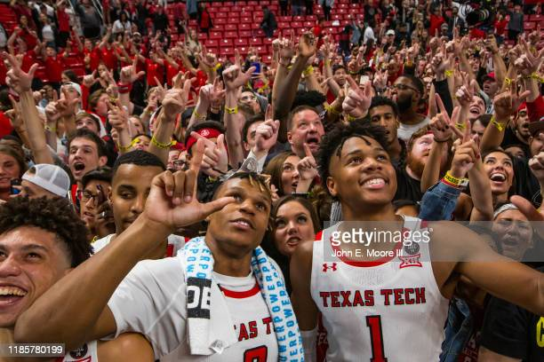 Members of the Texas Tech Red Raiders including guards Jahmi'us Ramsey and Terrence Shannon, along with head coach Chris Beard, celebrate with fans...