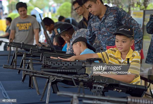 Members of the Thai military watch over children as they look at a display of guns during National Children's Day at a military base in Bangkok on...