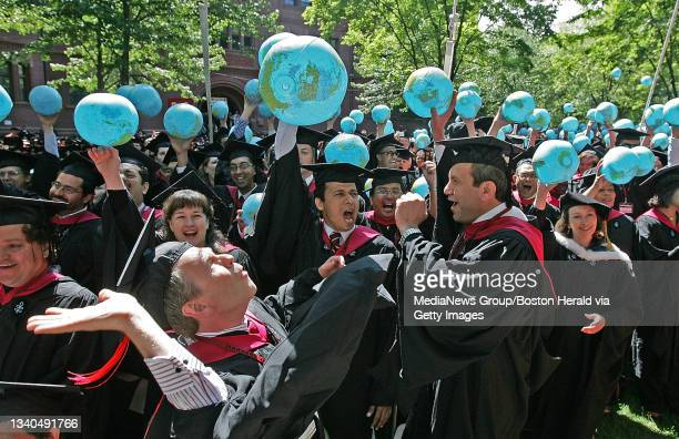 Members of the the Kennedy School of Government celebrate the conferring of their degrees by playing with inflatable globes at the Harvard University...