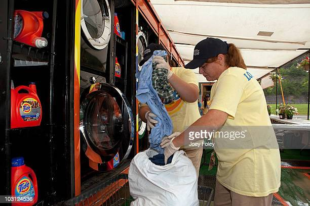 Members of the Tide's Loads Of Hope mobile laundry crew load a washing machine at the Tide's Loads Of Hope mobile laundry program at the Loads of...
