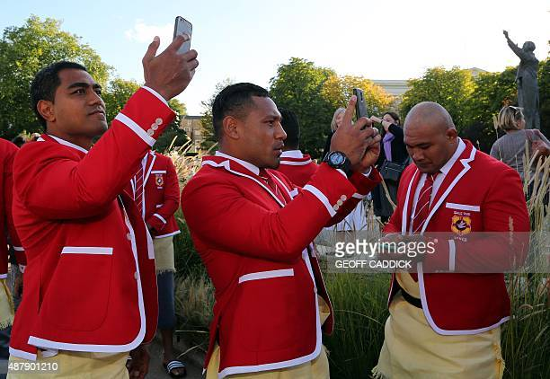 Members of the Tonga squad take self portraits with their mobile phones as they arrive for a 2015 Rugby Union World Cup welcoming ceremony at...