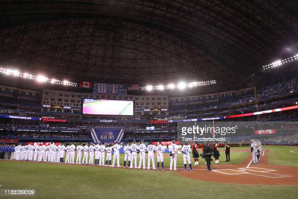 Members of the Toronto Blue Jays and Detroit Tigers line up along the baselines during the singing of the national anthems before the start of their...