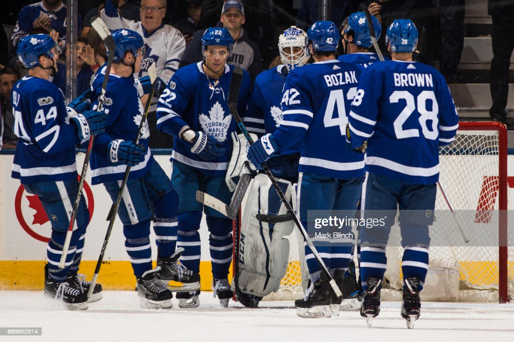 Members of the Toronto Maple Leafs congratulate Curtis McElhinney #35 after they defeated the Edmonton Oilers at the Air Canada Centre on December 10, 2017 in Toronto, Ontario, Canada.