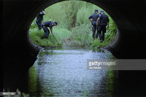 Members of the Toronto police public order unit scour a water course using bladeless hockey sticks in a search for potential evidence that might lead...