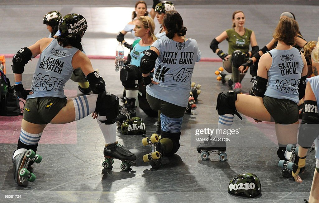 Members of the Tough Cookies team listen to their coach before competing against the Varsity Brawlers during the L.A. Derby Dolls women's banked track roller derby event in Los Angeles on April 17, 2010. Roller Derby is a contact sport that originated in America and is based on two teams formation roller skating around an oval track, with points scored as one player known as a jammer laps members of the opposing team. The sport which began in 1922 is played predominantly by women skaters with a strong emphasis on punk aesthetics, unique costumes and humorous stage names. AFP PHOTO/Mark RALSTON