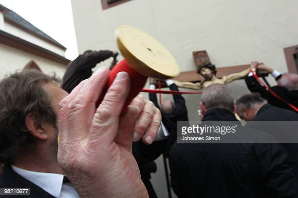 Members of the town's crafts guilds decorate a baroque sculpture Christ hanging on the cross during a Good Friday procession on April 2, 2010 in Lohr...
