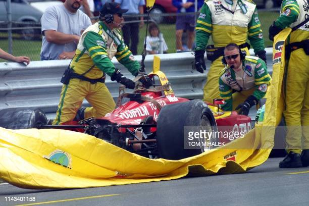 Members of the track clean-up crew remove the smashed car of Nicolas Minassian, of France, who drives for the CART Target team, after he crashed into...
