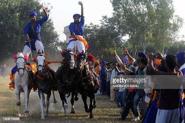 Members of the traditional Sikh religious warriors' Nihang Army perform on horseback on the occasion of 'Fateh Divas' in Amritsar on October 27 2011...