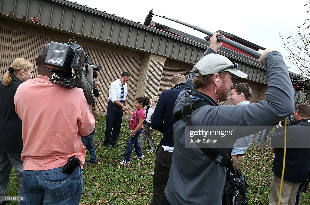 Members of the traveling press look on as Republican presidential candidate, former Massachusetts Gov. Mitt Romney (C) greets students at Fairfield Elementary school after he delivered a foreign policy speech at the Virginia Military Institute on October 8, 2012 in Fairfield, Virginia. Mitt Romney is campagning in Virginia.