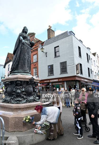 Members of the Traveller community place flowers at the Queen Victoria statue in Windsor, west of London, on April 12 three days after the death of...