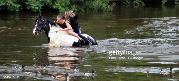 Members of the travelling community ride a horse in the river Eden at the start of the Appleby Horse Fair the annual gathering of gypsies and...